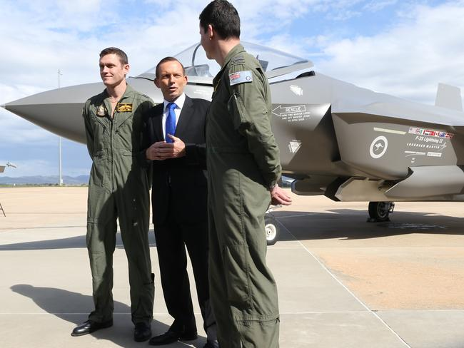 Imposing presence ... Prime Minister Tony Abbott with a mock-up of the F-35 Lightning II Joint Strike Fighter at RAAF base Fairbairn, in Canberra. Australia has committed to buying more than 70 of the controversial aircraft.