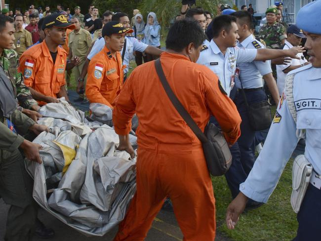 Indonesian air force personnel carry aeroplane parts recovered from the water near the site where AirAsia Flight 8501 disappeared, at the air base in Pangkalan Bun, Central Borneo, Indonesia. Picture: Dewi Nurcahyani