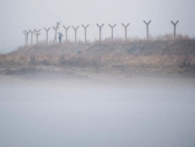 North Korean man holding an umbrella while standing at a border fence amid fog next to the Yalu river near Sinuiju, opposite the Chinese border city of Dandong. Picture: Johannes Eisele
