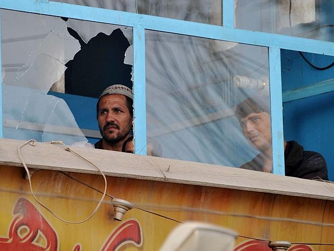 Taliban attack...Afghan residents look through shattered windows in the vicinity of a police station which was the scene of an attack in Jalalabad that killed 10 police officers. Piture: AFP