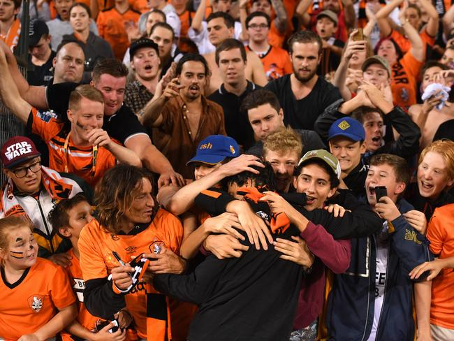 Roar player Thomas Broich is embraced by fans
