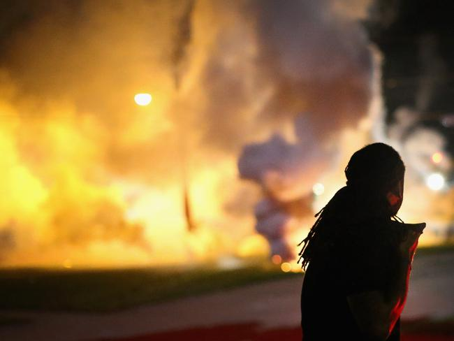 Up in smoke ... A protester scrambles for cover as police fire tear gas on August 13, 2014 in Ferguson, Missouri. The St Louis suburb has been rocked by a fourth day of protests over police violence. Picture: Getty