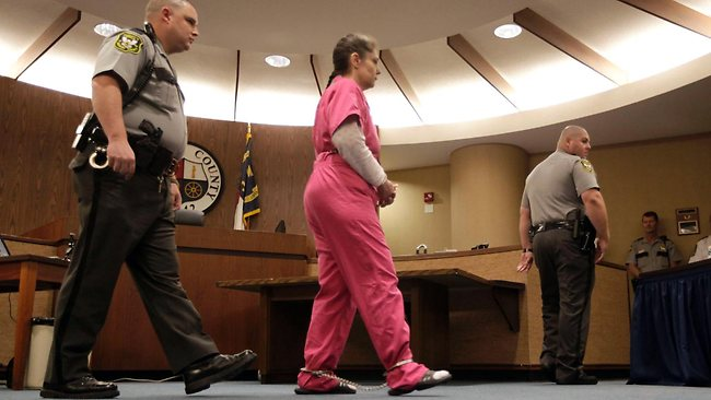Dressed in a pink jumpsuit, Elisa Baker is escorted into Catawba County court in Newton, North Carolina. Picture: AP