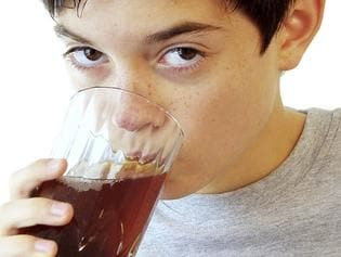 Boy drinking a glass of soft drink
