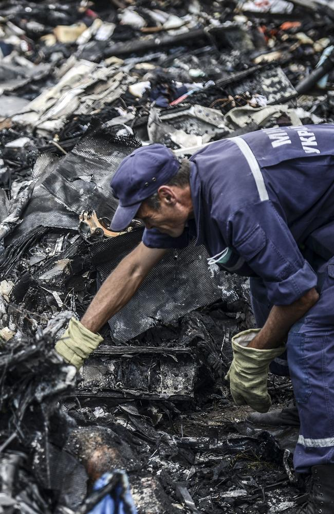 Grim task ... Ukrainian State Emergency Service employees search for bodies among the wreckage at the crash site of Malaysia Airlines Flight MH17.