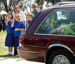 <p>School friends of the boys watch one of the hearses go by. Picture: Jon Hargest</p>
