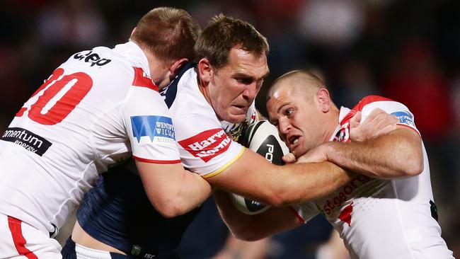 Scott Bolton is tackled by the Dragons defence.