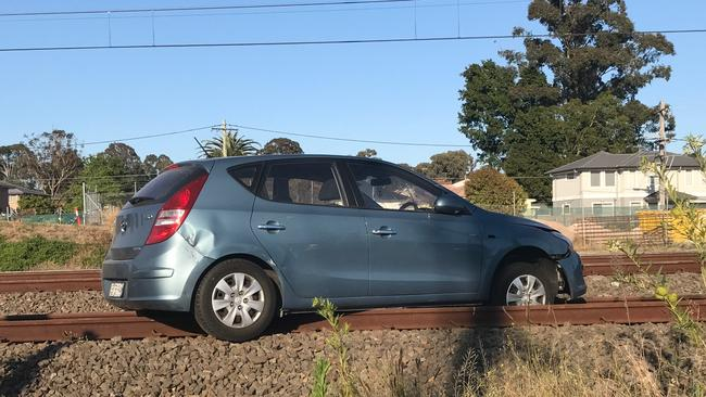 A car left the road and has became stuck on the railway lines near Toongabbie, western Sydney, this morning. Picture: Andrew Gibson.