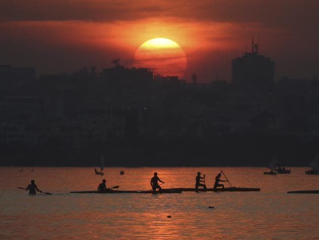 Spectacular ... Indians paddle on the Hussain Sagar Lake during this year's last sunset in Hyderabad, India. Picture: AP Photo/Mahesh Kumar