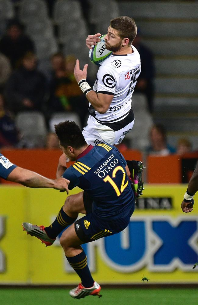 Sharks' Willie Le Roux (Top) is tackled by Highlanders' Jason Emery during the Super Rugby match between the Highlanders and Sharks at Forsyth Barr Stadium in Dunedin on April 22, 2016.