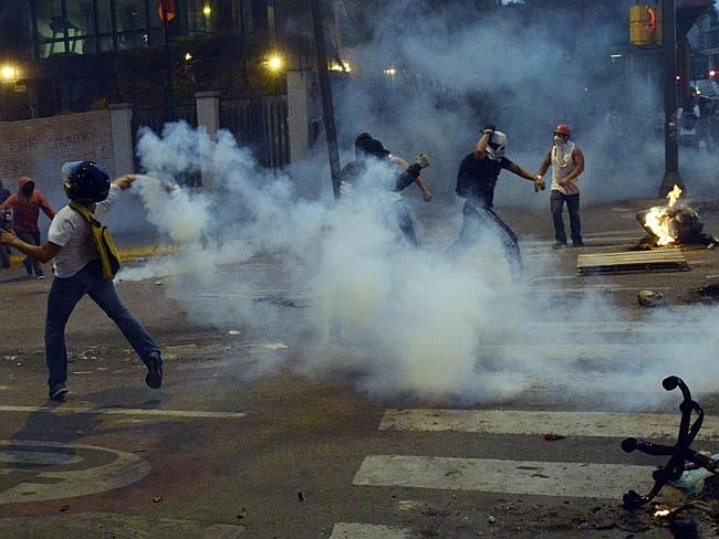Demonstrators clash ... with riot police during an anti-government protest in east Caracas. Picture: AFP /Juan Barreto
