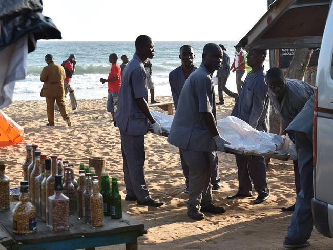 Employees load a body into a van after heavily-armed gunmen opened fire in the Ivory Coast resort town of Grand-Bassam, leaving bodies strewn on the beach.