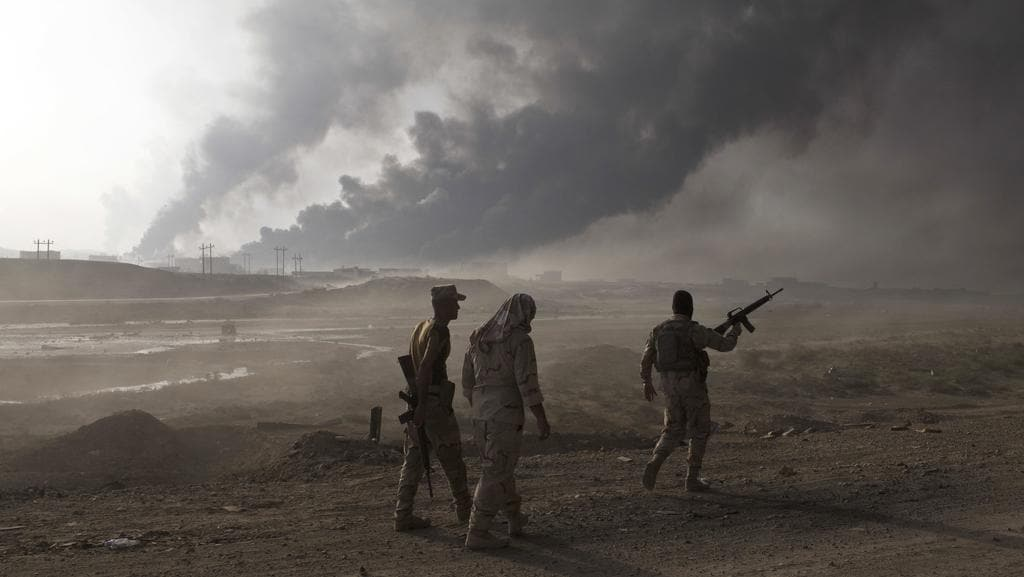 Iraqi army soldiers man a checkpoint as oil wells burn on the outskirts of Qayyarah, Iraq. Picture: AP Photo/Marko Drobnjakovic