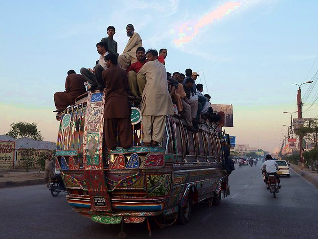 Pakistani passengers travel on a over loaded mini bus in Karachi. Picture: AFP