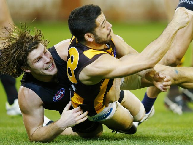 Paul Puopolo manages a handball clear as he is tackled by Bryce Gibbs. Pic: Michael Klein.