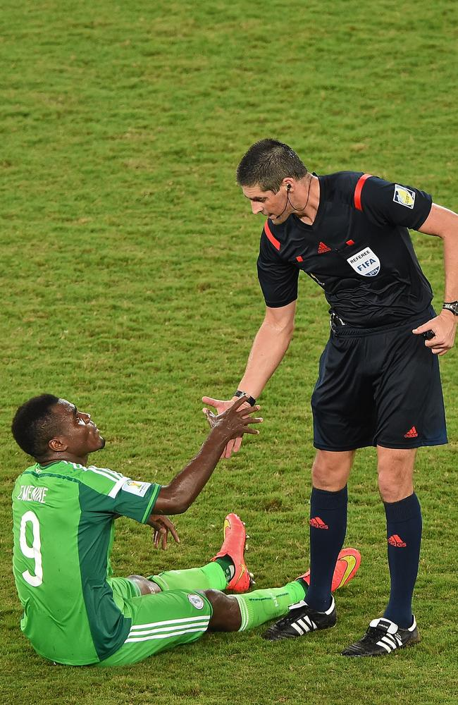 New Zealander referee Peter O'Leary helps Nigeria's forward Emmanuel Emenike stand up.