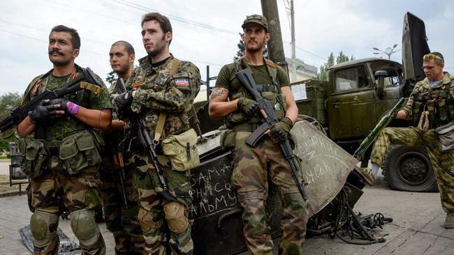 French volunteers, supporters of Pro-Russian rebels, stands near destroyed Ukrainian military machines at the Lenin square in the town of Donetsk, eastern Ukraine, Thursday, Aug. 28, 2014. (AP Photo/Mstislav Chernov)