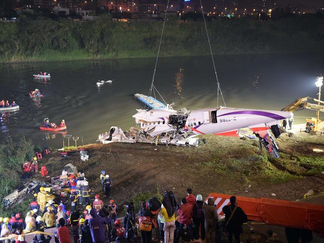 Rescuers lift the wreckage of the TransAsia ATR 72-600 out of the Keelung river. Picture: Sam Yeh