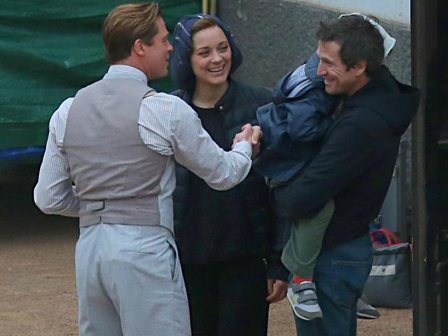 A dapper Brad Pitt meets the son and husband of his co-star Marion Cotillard while filming. Picture: Splash News