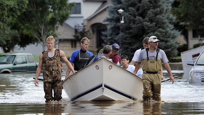 Eric Machmuller, front left, Brian Winn, rear left, Mitch Machmuller, rear right, and Pat Machmuller, front right, steer a boat down a residential street. Photo: AP