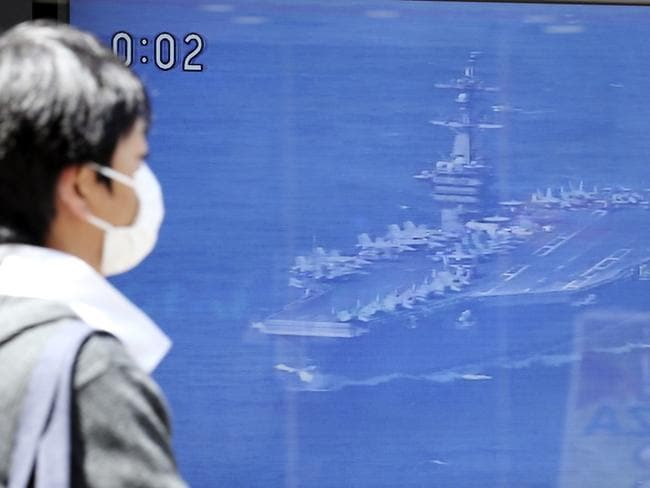 A man walks past a TV news showing an image of USS aircraft carrier Carl Vinson while reporting North Korea's missile test, in Tokyo. Picture: AP