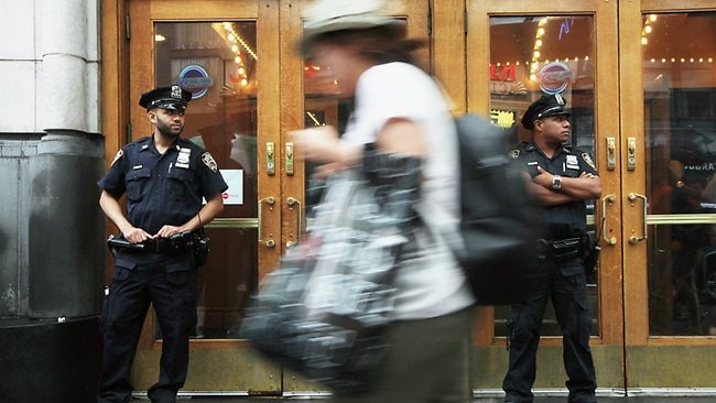 NYPD officers keep watch in front of an AMC move theater where the film 'The Dark Knight Rises' is playing in Times Square. Picture: Mario Tama / Getty