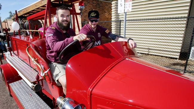 Nate Myles drives a vintage fire engine with Chris McQueen.