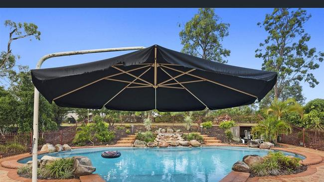 A large umbrella by the pool can be rotated.