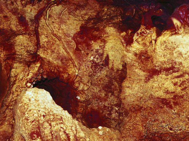 This colour enhanced image shows three hand stencils in the Maltravieso Cave in Spain. One has been dated to at least 66,000 years ago. Picture: Collado Giraldo