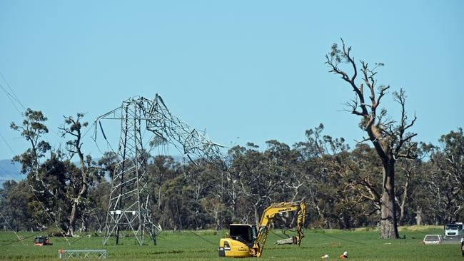 A digger works near a damaged power tower near Melrose in the state's mid north.