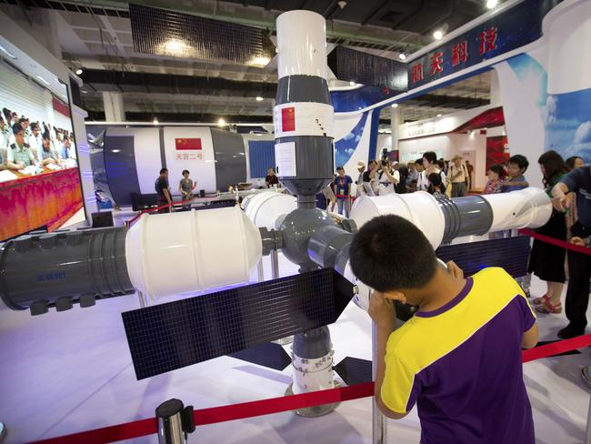 Visitors look at a model of China's Tiangong-1 space station in Beijing. Picture: AP/Mark Schiefelbein