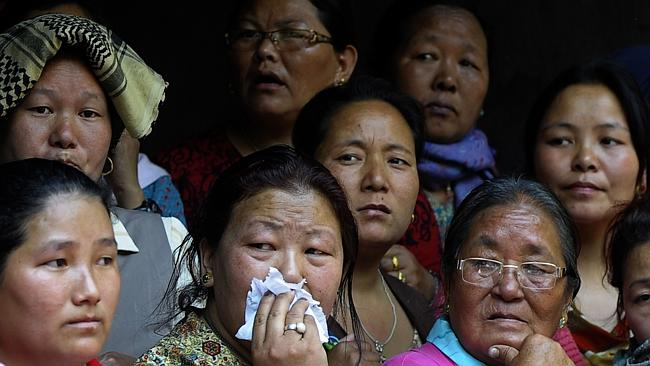 Unbearable ... grief-stricken relatives of the sherpas look on during the cremation ceremony.