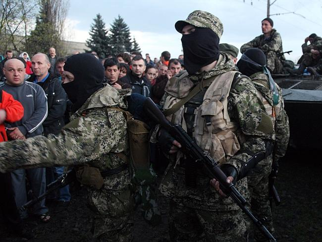 Standing firm ... armed pro-Russia activists block a collumn of Ukrainian men riding on Armoured Personnel Carriers in the eastern Ukrainian city of Kramatorsk. Picture: Anatoliy Stepanov