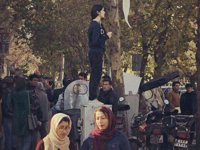 A lone Iranian woman having removed her hijab became a powerful image of the uprising.