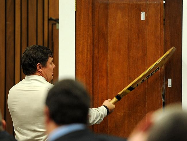 Match point ... Police forensic expert Colonel Johannes Vermeulen hits a door with a cricket bat in a re-enactment of how South African Paralympian Oscar Pistorius broke down the door of the toilet where he shot dead his girlfriend. Picture: Werner Beukes