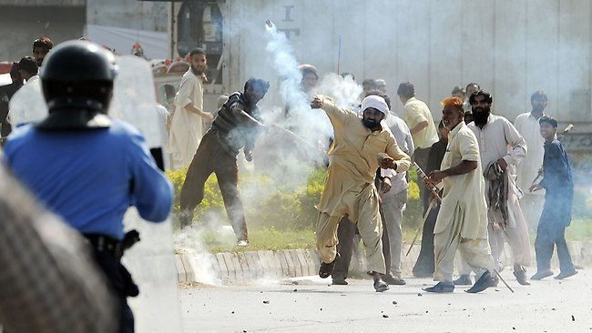 "A Pakistani demonstrator throws a tear gas shell towards riot police during a protest against an anti-Islam film in Islamabad on September 21, 2012. Angry demonstrators set fire to two cinemas in Pakistan's northwestern city of Peshawar, police and witnesses said, as the country began a day of protests against an anti-Islam film. Pakistan's Prime Minister Raja Pervez Ashraf urged people to vent their fury peacefully over the ""Innocence of Muslims"" film, which has triggered angry demonstrations around the world. AFP PHOTO/ AAMIR QURESHI"