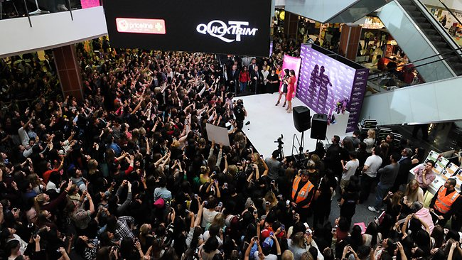 Kim Kardashian, left, on stage looks over the crowd of fans during a public event at Southlands shopping center in Melbourne. Picture: AP