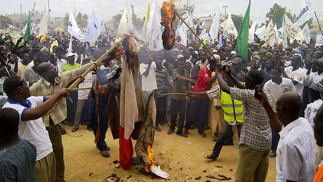 "Protesters burn US and Israeli flags and a portrait of US president Barak Obama at the end a protest march against the US-produced anti-Islam movie in the northern Nigerian city of Kano on September 22, 2012. Tens of thousands of people protested on the streets of Nigeria's second city of Kano against an anti-Islam film made in the US that has stirred outrage across the Muslim world. An AFP reporter said the crowd of demonstrators stretched several kilometres through the city, the largest in Nigeria's mainly Muslim north, with protesters shouting ""death to America, death to Israel and death to the enemies of Islam"". AFP PHOTO / Aminu ABUBAKAR"
