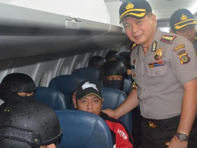So who did take the snap ... Denpasar police chief commissioner Djoko Hari Utomo puts his hand on Andrew Chan's shoulder and poses for a picture on the flight from Bali to Cilacap where Chan is to be executed. Picture: Supplied