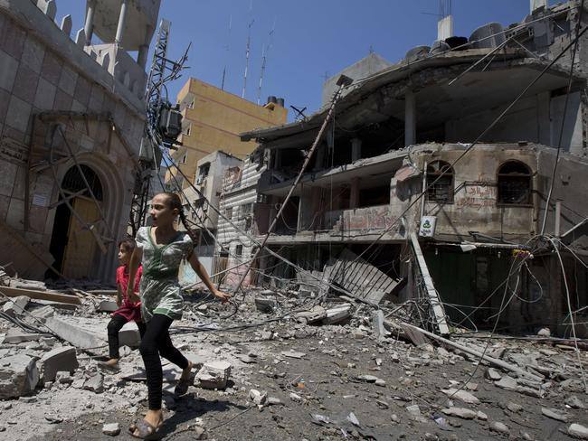 War zone. Palestinian girls walk amid debris following an Israeli military strike in Gaza city, on July 23. Picture: AFP