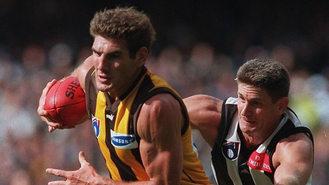 Hawthorn's Nick Holland is pursued by Collingwood's Gavin Crosisca. Picture: Colleen Petch