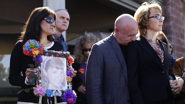 Roxanna Green holds a photo of her daughter Christina Taylor Green, who was killed in the January 8, 2011 Tucson shooting, as Mark Kelly leans his head on the shoulder of his wife, former U.S. Rep. Gabby Giffords.