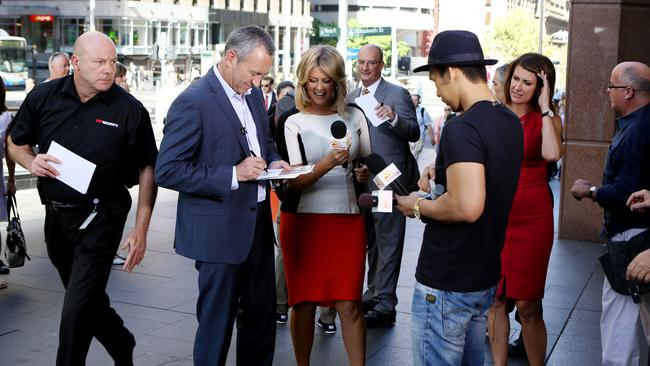 Meeting the fans ... The Sunrise crew sign autograph cards in Martin Place.
