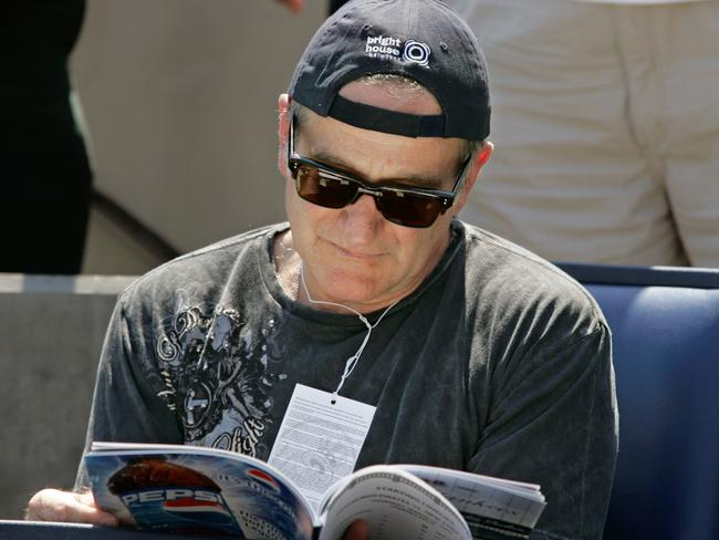 Actor and comedian Robin Williams thumbs through a program before the start of a Yankees baseball game in Florida.