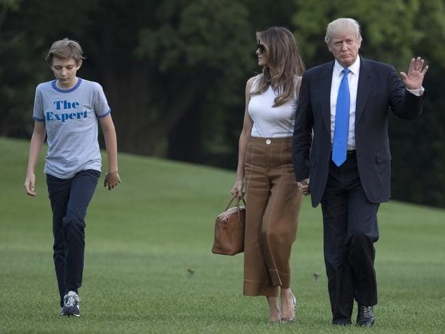President Donald Trump waves as he walks with first lady Melania Trump and their son, Barron Trump, from Marine One across the South Lawn to the White House. Picture: AP Photo/Carolyn Kaster