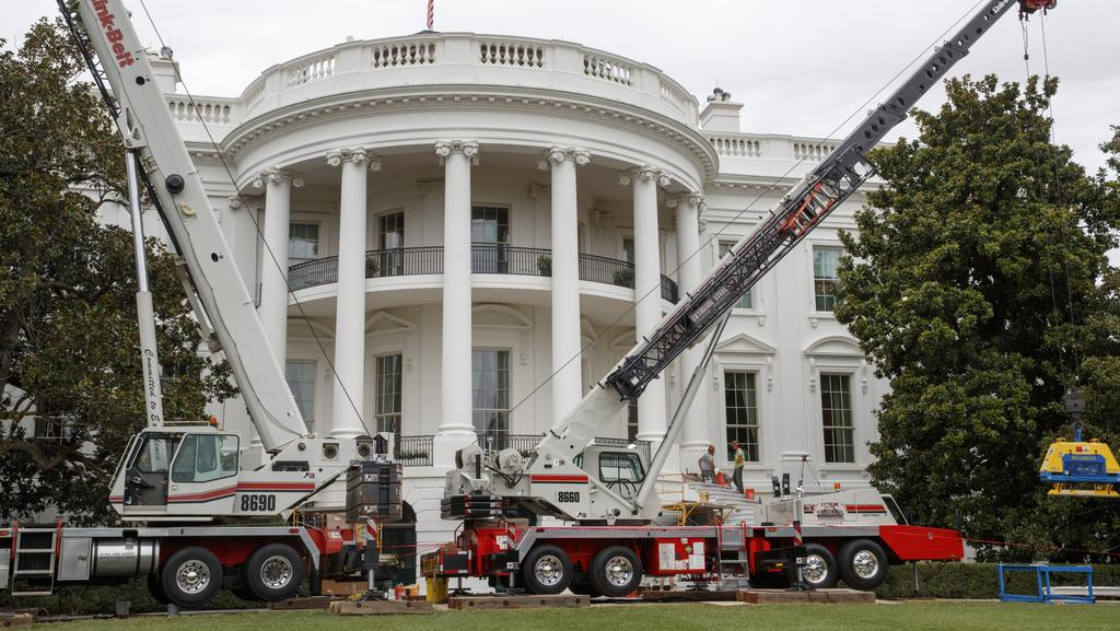 Cranes are positioned in front of the South Portico of the White House during renovations while President Donald Trump is spending time at his golf resort in New Jersey. Picture: AP