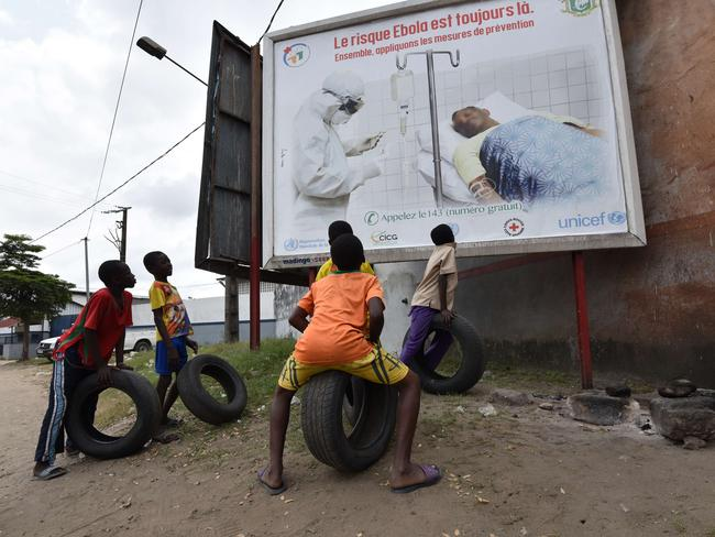 "Children look at a poster warning of the dangers of the Ebola virus reading ""the risk Ebola is still there. Let's apply the protective measures together"". Picture: Sia Kambou"