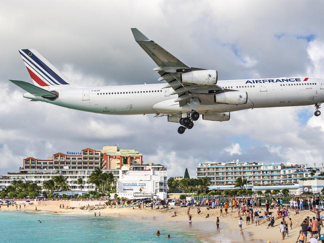 A commercial jet approaches Princess Juliana airport above onlooking spectators. The short runway gives beach goers close proximity views of the planes. Picture: Getty