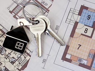 Keys with home on blueprints. Property real estate. moving into a new home. mortgage