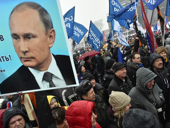 People hold a placard with the picture of the Russian President during a rally in support to Russian athletes this month. Picture: Vasily Maximov/AFP